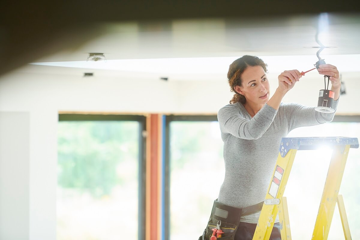 Image of woman making repairs and upgrades to her rental property before selling.