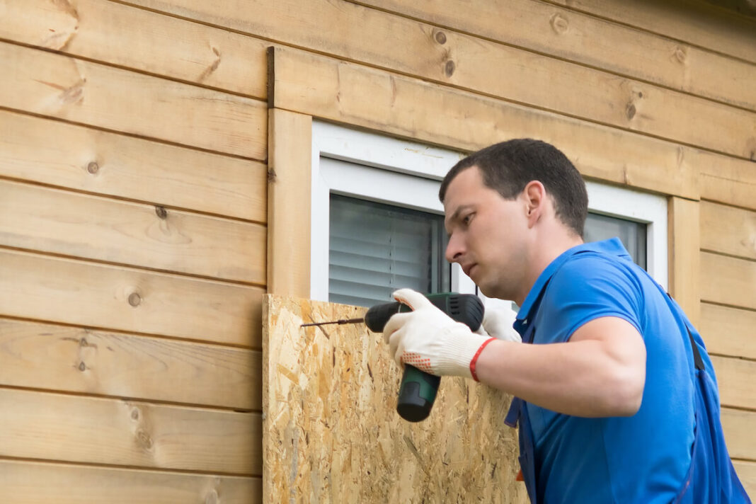 Image of man preparing for hurricane by boarding up windows.